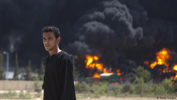 Power station in Gaza on fire, with a young man standing in the foreground. (Photo: MAHMUD HAMS/AFP/Getty Images)