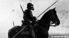 2nd August 1917: A German cavalryman wearing a gas mask and carrying a long spear or pole - from two different ages of war. (Photo by Topical Press Agency/Getty Images)