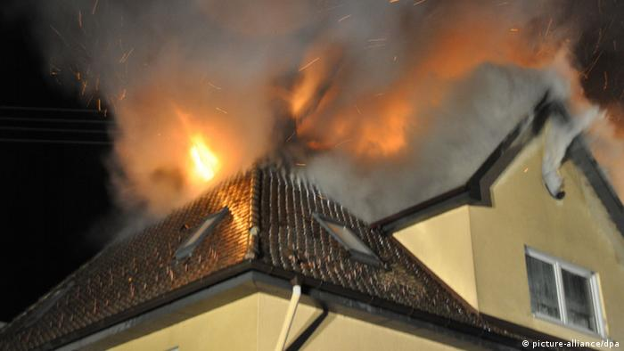 the roof of a house with a yellow facade is on fire
