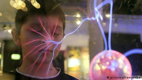 A boy stands behind a glas ball whit an artificial lightning