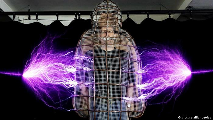 A man in a metal mesh suit is struck by lightnings from left and right