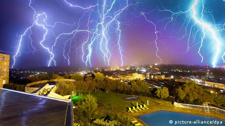 Several thunderbolts light up the sky over a city