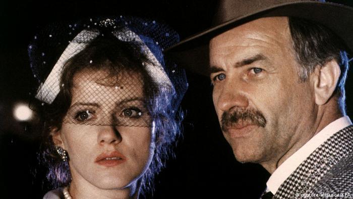 Man mit Schnurrbart und Hut schaut mit einer elegant gekleideten Frau in die Ferne