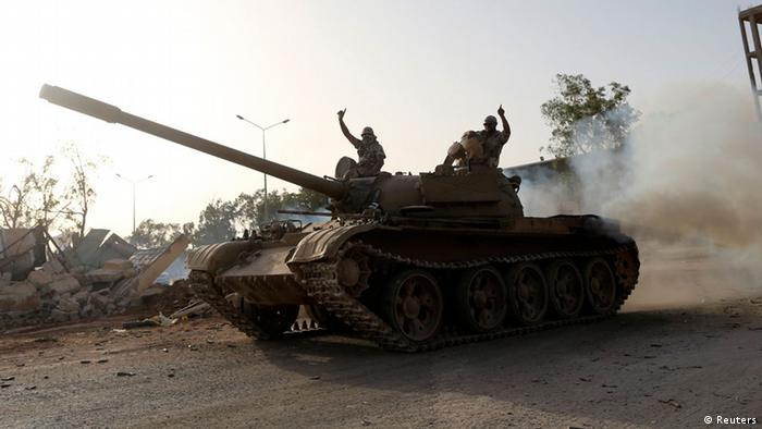 Fighters from the Benghazi Shura Council, which includes former rebels and militants from al Qaeda-linked Ansar al-Sharia, gesture on top of a tank next to the camp of the special forces in Benghazi July 30, 2014. On Wednesday, the eastern city of Benghazi was quieter after Islamist fighters and allied militia forces overran a special forces army base in the city in a major blow to a military campaign against Islamist militants there. The self-declared Benghazi Shura Council forces took over the base on Tuesday after fighting involving rockets and warplanes that killed at least 30 people. REUTERS/Stringer