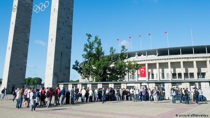 People are queing in front of a building with a Turkish flag (Foto: Maurizio Gambarini/dpa)