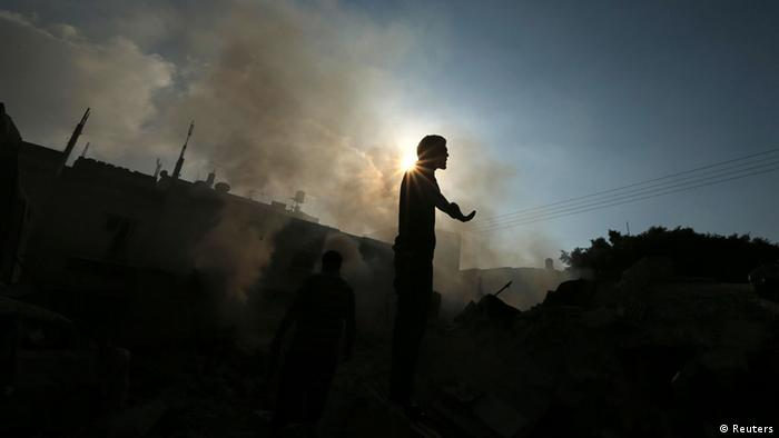 A Palestinian standing atop the remains of a house, which witnesses said was destroyed in an Israeli air strike, reacts as smoke rises in Gaza City July 31, 2014, Copyright: Reuters