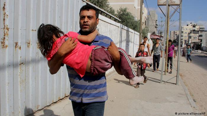 Man fleeing with child (Photo: AP Photo/Hatem Ali)