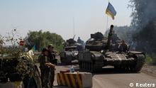Ukrainian army tanks move past a checkpoint as they patrol the area near eastern Ukrainian town of Debaltseve August 3, 2014. Nine civilians were killed in new fighting between government forces and pro-Russian separatists around the cities of Luhansk and Donetsk in east Ukraine, local officials said on Sunday. REUTERS/Valentyn Ogirenko (UKRAINE - Tags: CIVIL UNREST CONFLICT)