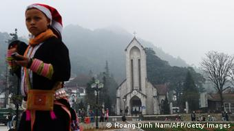 A Dao ethnic woman on her Sunday best waiting for friends on the church square in downtown of the popular tourist district of Sapa, northern mountainous province of Lao Cai.