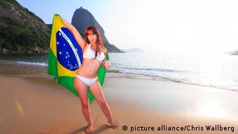 Frau mit Brasilienflagge am Strand (Foto: picture alliance)