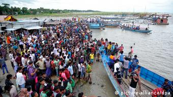 A beach on the banks of the river Padma crowded with people.