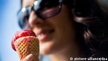 ARCHIV - Eine junge Frau isst am 23.08.2011 in Düsseldorf eine Kugel Eis aus einer Waffel. Laut Wettervorhersage ist auch in den kommenden Tagen in Nordrhein-Westfalen mit sommerlichen Temperaturen zu rechnen. Foto: Victoria Bonn-Meuser/dpa (zu dpa «Waffel oder Becher? Eis-Fans äußern Vorliebe in Umfrage» vom 07.06.2014) +++(c) dpa - Bildfunk+++