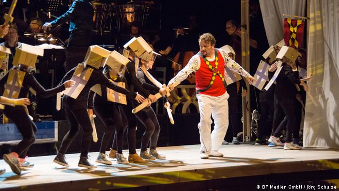 Lohengrin staging: Children with boxes on their heads and a man wearing a red suit.