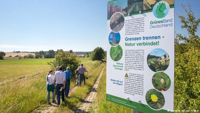 Un grupo de personas pasa por delante de una señal en la reserva natural de Grünes Band.