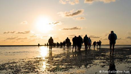 Wattwanderer bei Sonnenuntergang