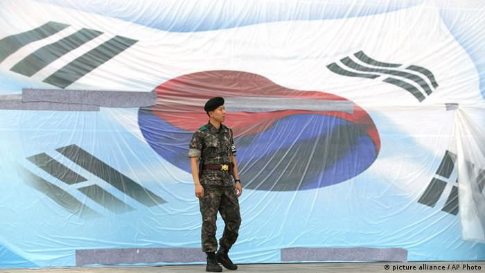 A South Korean soldier stands in front of huge national flag covered with plastic for protection on the eve of Memorial Day ceremony at the National Cemetery in Seoul, South Korea, Wednesday, June 5, 2013.