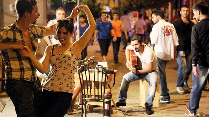 Man playing guitar, couple dancing in Turkey