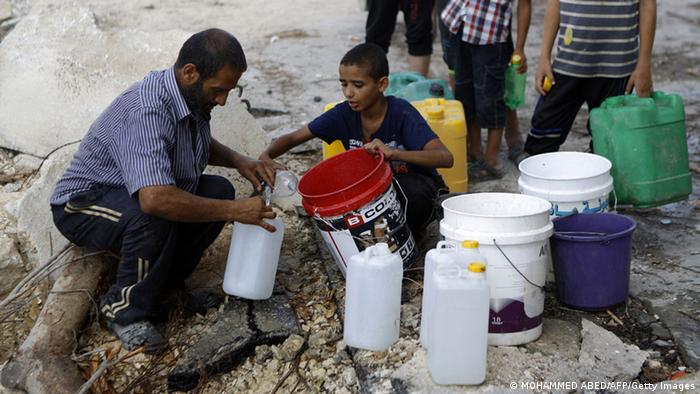 People in Gaza collect water in buckets