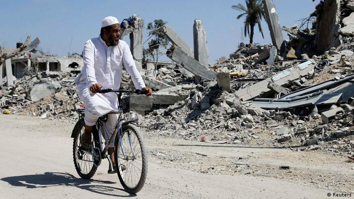 Gaza destroyed a picture from August 6th of a man on a bicycle riding past ruined buildings.