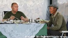 Russian Prime Minister Vladimir Putin takes lunch with a local villager during his vacation outside the town of Kyzyl in Southern Siberia on August 3, 2009. AFP PHOTO / RIA-NOVOSTI / ALEXEY DRUZHININ (Photo credit should read ALEXEY DRUZHININ/AFP/Getty Images)