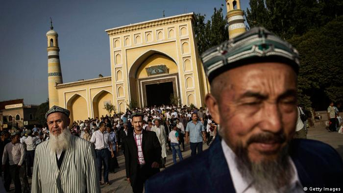 A Uighur man with a beard stands in front of a mosque in Xinjiang