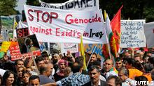 Kurds of the ethnic minority of Yazidis hold up a banner reading Stop genocide against Yazidis in Iraq as they march through the streets of Bielefeld August 9, 2014. Some 10,000 ethnic Kurds of the Yazidis sect, who practice an ancient faith related to Zoroastrianism, protested in the western German city on Saturday against Islamic State (IS) militants, who are surging across northern Iraq near the Kurdistan borders in their drive to eradicate unbelievers such as Christians and Yazidis. REUTERS/Wolfgang Rattay (GERMANY - Tags: CIVIL UNREST POLITICS RELIGION)