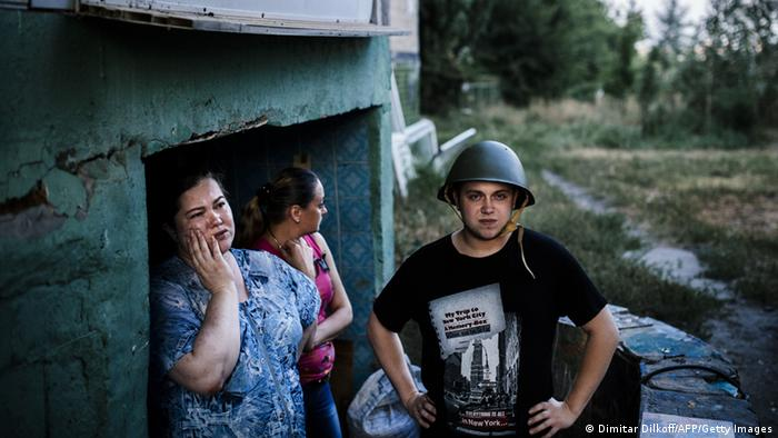 People at the entrance of a makeshifr bomb shelter