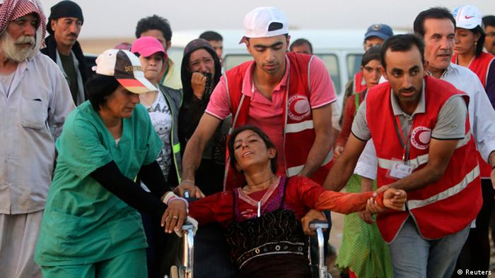 Mitglieder des kurdischen Roten Halmondes helfen am Rande des Sindschar-Gebirges ankommenden Flüchtlingen. Foto: REUTERS/Rodi Said