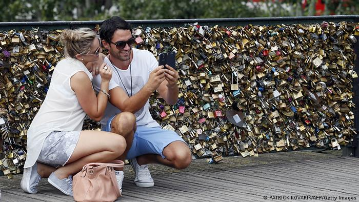 A couple takes a photo in front of love locks on Paris' Pont des Arts Bridge.