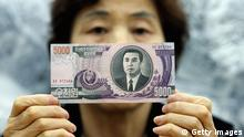 SEOUL, SOUTH KOREA - FEBRUARY 14: A North Korean asylum seeker who is now an anti-North Korea activist shows a KPW 5,000 (North Korean Won) banknote to be dropped with leaflets over North Korea by balloon, at an office on February 14, 2009 in Seoul, South Korea. The balloons containing anti-Pyongyang leaflets will be released on February 16, the birthday of Kim Jong-il. For the first time the balloons will also release North Korean banknotes. (Photo illustration by Chung Sung-Jun/Getty Images)