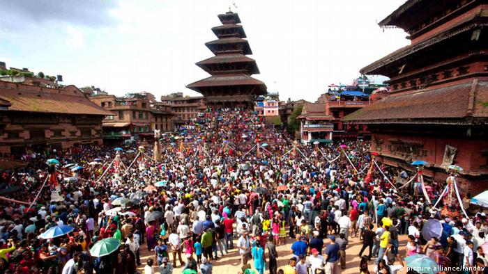 A square in Katmandu full of people celebrating Gaijatra.