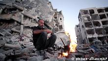 Palestinian Ziad Rizk, 38, makes coffee next to one of the destroyed Nada Towers, where he lost his apartment and clothes shop, in the town of Beit Lahiya, northern Gaza Strip, Monday, Aug. 11, 2014. (AP Photo/Khalil Hamra)