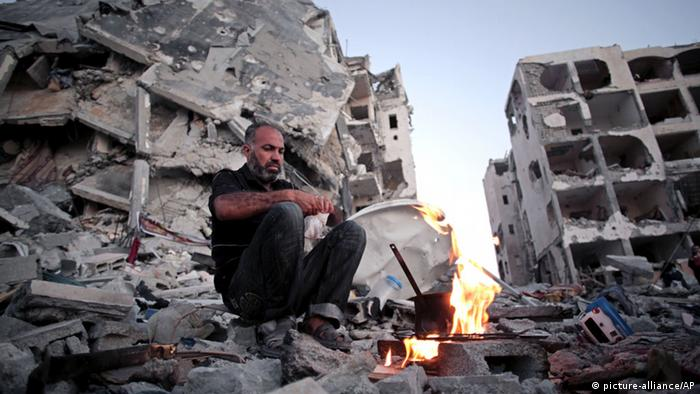 Man makes coffee next to one of the destroyed Nada Towers