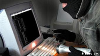 A man in a robber's mask in front of a computer