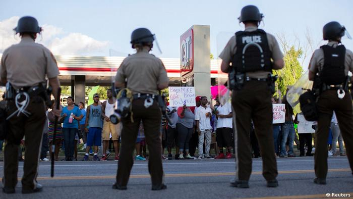 Police officers watch as demonstrators protest the death of black teenager Michael Brown in Ferguson, Missouri. Photo: REUTERS/Mario Anzuoni