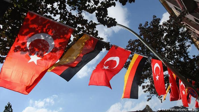 Türkische und deutsche Flaggen hängen nebeneinander unter einem Baum