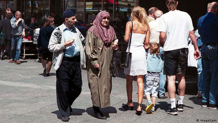 People walking in Berlin, including a woman in a headscarf