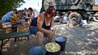 Ukrainerin kocht in einem Flüchtlingscamp Kartoffeln. Foto: EPA/SERGEI KOZLOV