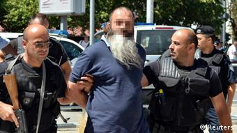 A bearded middle-aged man of Middle Eastern descent is led away, handcuffed, by police