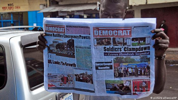 Liberia Westafrika Mann ließt Zeitung über Ebola