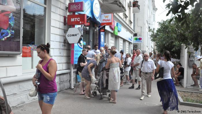 A group of people waiting outside a mobile phone shop in Sevastopol Photo: Jurij Terechow / DW