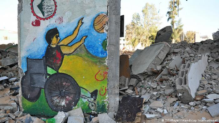 A section of wall depicting a wheelchair user with a ball stands among heaps of rubble
