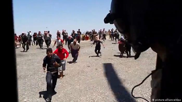 Jesidische Flüchtlinge versuchen, sich in einen Hubschrauber zu retten. Foto: Michel Reimon, dpa.