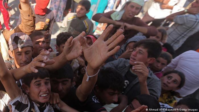 Jesiden auf der Flucht in Nordirak bei der Verteilung von Wasserflaschen. Foto: AFP PHOTO/AHMAD AL-RUBAYE