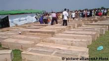 Coffins are laid out as Tutsi refugees from Congo, who survived a massacre by Hutu extremists at the U.N.-run camp in Gatumba, Burundi, began the grim task Sunday Aug.15 2004 of identifying 150 bodies of relatives and friends who were shot, hacked and burned to death in ethnic violence reminiscent of the 1994 genocide in neighboring Rwanda. A Burundian Hutu rebel group claimed responsibility for the attack late Friday on the refugee camp in Gatumba, which sheltered Congolese Tutsis known as Banyamulenge who had fled fighting in their troubled country. (AP Photo/Aloys Niyoyita)