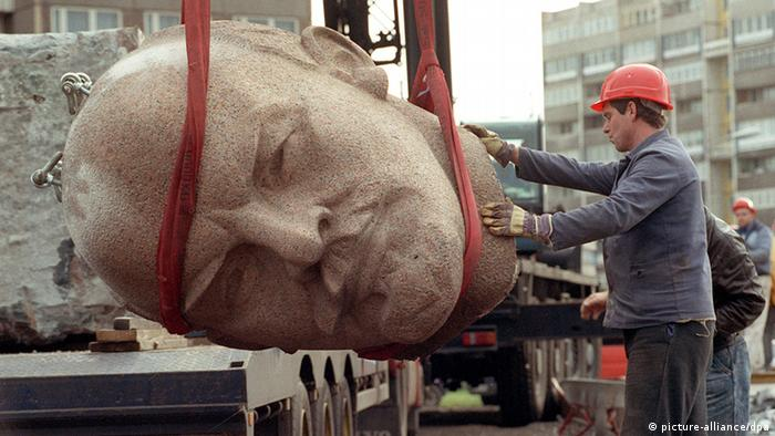 A worker stands next to the head of the Lenin monument as it is dismantled in 1991