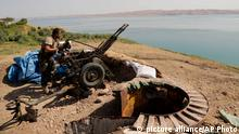 A Kurdish peshmerga fighter prepares his weapon at his combat position near the Mosul Dam at the town of Chamibarakat outside Mosul, Iraq, Sunday, Aug 17, 2014. Kurdish forces took over parts of the largest dam in Iraq on Sunday less than two weeks after it was captured by the Islamic State extremist group, Kurdish security officials said, as U.S. and Iraqi planes aided their advance by bombing militant targets near the facility. (AP Photo/Khalid Mohammed)