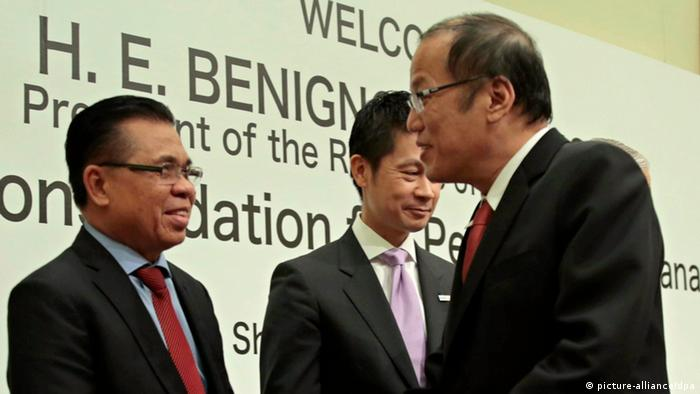 BeA handout photo dated 24 June 2014 and released on 26 June 2014 by the Malacanang Photo Bureau shows Philippine President Benigno Aquino III (R) and Moro Islamic Liberation Front (MILF) chairman Murad Ebrahim (L) shaking hands during a meeting on the sidelines of a peace conference in Hiroshima city, Japan.