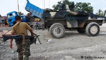 An armed soldier walks on July 22, 2014 in the town proper of Datu Salibo, Mindanao, Philippines.The Filipino military have reported that 18 people have been killed after Fighting broke out between the Philippine army and a breakaway Muslim rebel group in the country's south killed.