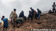 Bildunterschrift:Indian residents and security personnel dig through mud following heavy rainfall and landslides in the Pauri district of the state of Uttarakhand on August 15, 2014. A landslide and floods triggered by extremely heavy rainfall killed 17 people in northern India on August 15, 2014, authorities said. Another six people were left with injuries in the small remote Himalayan state of Uttarakhand by the downpours. Fourteen people were killed when their houses were buried by a tide of mud and trees, emergency official Piyush Rautela told AFP. 'The bodies have been recovered,' he said. While India's annual rains are a lifeline for the country's farm sector, flooding, landslides and building collapses are frequent during the monsoon season, which sweeps India from June to September. AFP PHOTO/STR (Photo credit should read STRDEL/AFP/Getty Images)